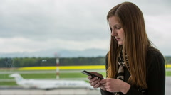 Woman at airport typing on smartphone Stock Footage