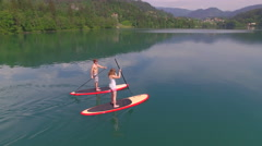 AERIAL: Young couple SUP boarding on stand up paddle board in sunny summer Stock Footage