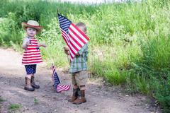 Toddlers having fun in the park for July Fourth - stock photo