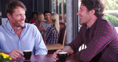 Two Mature Male Friends Sitting In Coffee Shop Chatting Stock Footage