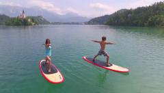 AERIAL: Flying around young couple doing yoga on SUP boards Stock Footage