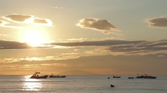 Luminous Burnished Gold Sea Sunset with Boats Swimmers and Clouds 1 - stock footage