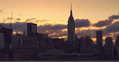 Golden clouds passing by the Empire State Building in the Manhattan skyline Arkistovideo