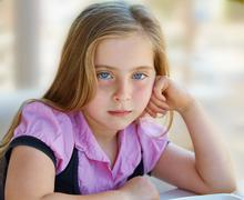 Blond relaxed sad kid girl expression blue eyes Stock Photos