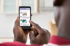 Close-up Of African Young Man Surfing On Social Networking Site Using Cellpho Kuvituskuvat