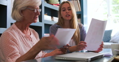 Daughter Helping Senior Mother With Paperwork In Home Office Stock Footage