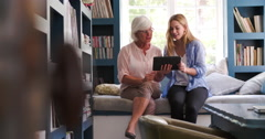 Daughter Helping Senior Mother With Digital Tablet At Home Stock Footage