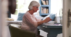 Senior Woman At Desk Working In Home Office With Laptop - stock footage