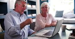 Senior Couple In Home Office Looking At Laptop And Arguing - stock footage