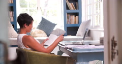 Mature Woman Sitting At Desk Reading Book In Home Office Stock Footage