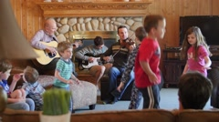 A family playing music and children dance at a party - stock footage