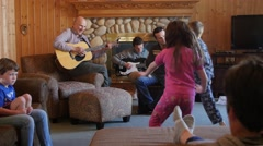 A family playing music and children dance together at a party - stock footage