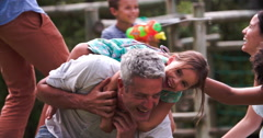 Slow Motion Sequence Of Families Playing In Garden Together Stock Footage