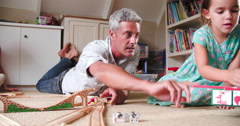 Father And Daughter Playing With Train Set In Bedroom Stock Footage