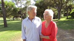 Senior Couple Walking Through Park Talking Stock Footage