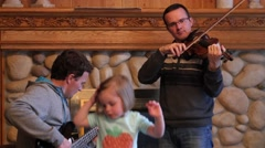 A family plays music and dances together at a party Stock Footage