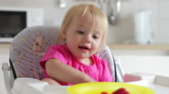 Young Girl Sitting In High Chair Eating Strawberry Stock Footage