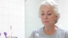 Senior Woman Reflected In Bathroom Mirror Brushing Teeth Stock Footage