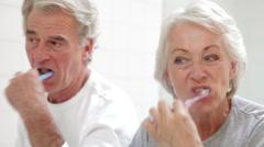 Senior Couple Reflected In Bathroom Mirror Brushing Teeth Stock Footage