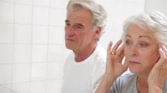 Senior Couple Checking Skin In Bathroom Mirror Stock Footage