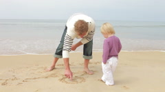 Father And Young Daughter At Beach Drawing Pictures In Sand Stock Footage