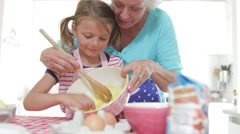 Grandmother And Granddaughter Baking In Kitchen Stock Footage