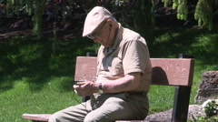 Old man sitting on a bench outside in the summer in their retirement years Stock Footage