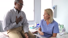 Doctor Writing Up Notes For Middle Aged Male Patient - stock footage