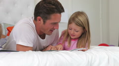 Family Lying In Bed Reading Books Together Stock Footage