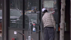 A restaurant worker cleaning windows in Manhattan Stock Footage