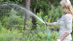 Middle Aged Woman Watering Garden With Hosepipe Stock Footage