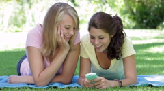Two Teenage Girls Lying In Garden Reading Text Message Stock Footage