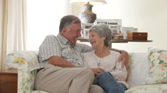 Retired Senior Couple Sitting On Sofa At Home Together Stock Footage