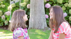 Teenage Girl Talking To Younger Sister In Garden Stock Footage