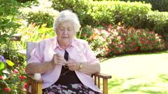Senior Woman Doing Crochet Whilst Sitting In Garden - stock footage