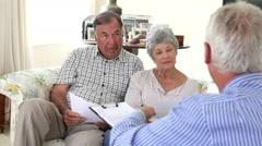 Senior Couple Sitting On Sofa Talking To Financial Advisor - stock footage