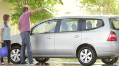Father And Teenage Daughter Washing Car Together Stock Footage