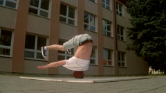Breakdancer spins on his head on the street, slowmotion Stock Footage