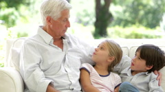 Grandfather With Grandchildren Sitting On Sofa At Home Stock Footage