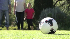 Family Running To Kick Football In Garden Stock Footage