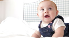 Cute Baby Girl Lying On Bed And Rolling Over Stock Footage