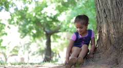 Young Girl Playing Game Sitting On Tree In Park Stock Footage