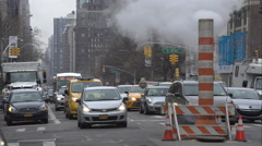 Traffic moving around a steaming smoke stack on 2nd Avenue in Manhattan Stock Footage