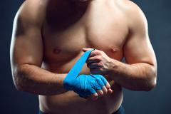 Muscular boxer bandaging his hands on gray background Stock Photos