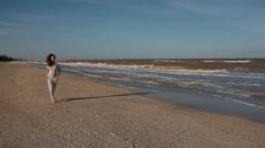 Young caucasian couple run along seaside Stock Footage