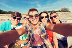 group of smiling friends making selfie outdoors - stock photo