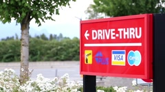 Red drive-thru sign with traffic flow background Stock Footage
