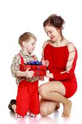 Fashionable mom gives her young son in the box Stock Photos