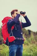 man with backpack and binocular outdoors - stock photo