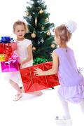 Girls sisters around the Christmas tree fuss considering boxes w Stock Photos